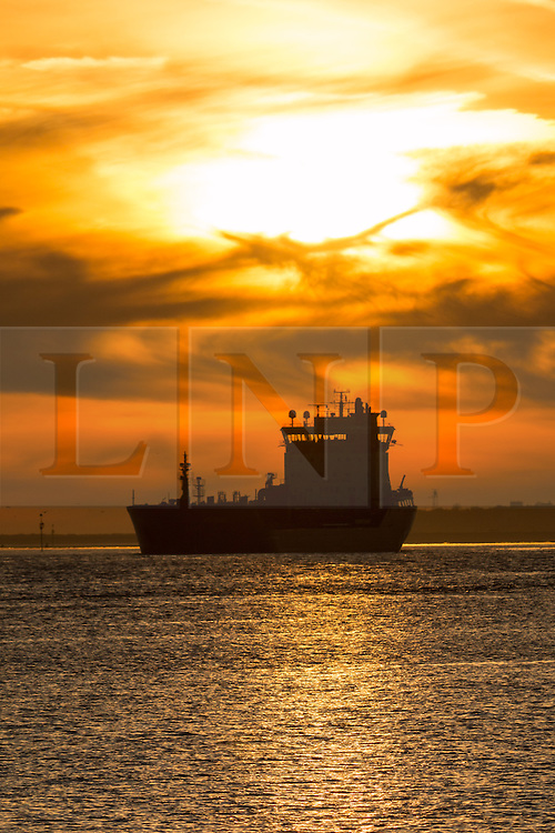 © Licensed to London News Pictures. 14/04/2015.  Tanker Futura makes her way up the Thames at sunrise this morning, seen here from Gravesend.  Tuesday 14th April got started with a deep Turneresque sky over the Thames estuary. Several days of good weather are predicted and Gravesend is often the location where the highest temperatures are recorded. Credit : Rob Powell/LNP