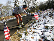 "Adriana Sparks pauses during her run Feb. 26 to read the names of 41 fallen Soldiers from 5th Bde., 2nd Inf. Div. who are memorialized each week at the ""wear blue: run to remember"" runs at Powderworks Park in DuPont."