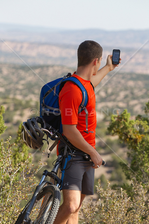 male bicyclist stopping to take a photograph with his cell phone in Santa Fe, New Mexico
