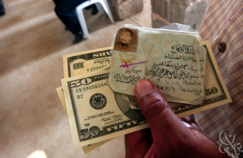Former Iraqi Army 1st Lieutenant Ryad Al Zubaydi holds his military ID and an emergency cash payment of $80 (USD) at American Army post in central Baghdad July 21, 2003. Former Iraqi soldiers expected compensation four up to 4 months, but were only being given payment for the month of the war.