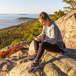 """A young woman checks her mobile phone from the trail on """"The Beehive"""" in fall in Maine's Acadia National Park.`"""