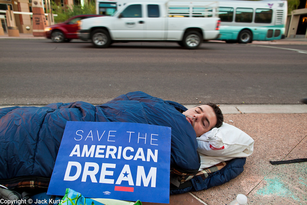 17 OCTOBER 2011 - PHOENIX, AZ:   Morning traffic passes BRIAN KORSEDAL, from Phoenix, AZ, while he sleeps on the sidewalk during the Occupy Phoenix protest Monday. About 40 people spent Sunday night on the sidewalks around the Cesar Chavez Plaza in Phoenix, AZ, the defacto headquarters of the Occupy Phoenix protest. Early Monday morning they got up to continue their chants and protests against Wall Street, the growing income gap between rich and poor in the US, and money in politics. Monday marks the third day of Occupy Phoenix.    PHOTO BY JACK KURTZ