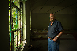 """Just down the road from Lindytown, West Virginia, Leo Cook looks out a window of the now-vandalized building that once served as the meeting hall for members of Local 8377 of the United Mine Workers of America. Back when the building was in use, Cook sometimes polished its wooden floors. Mountaintop-removal mines are now abundant in the area. Mountaintop Removal is a method of surface mining that literally removes the tops of mountains to get to the coal seams beneath. It is the most profitable mining technique available because it is performed quickly, cheaply and comes with hefty economic benefits for the mining companies, most of which are located out of state. Many argue that they have brought wage-paying jobs and modern amenities to Appalachia, but others say they have only demolished an estimated 1.4 million acres of forested hills, buried an estimated 2,000 miles of streams, poisoned drinking water, and wiped whole towns from the map. The mountaintop-removal mine near Blair caused the population to fall from 700 in the 1990s to fewer than 50 today, according to the Blair Mountain Heritage Alliance. """"I saw Lindytown disappear,"""" Leo Cook said. """"Three people up there that died, and I believe in my soul -- I'll go to my grave believin' this?that aggravation's what caused it."""" © Ami Vitale"""