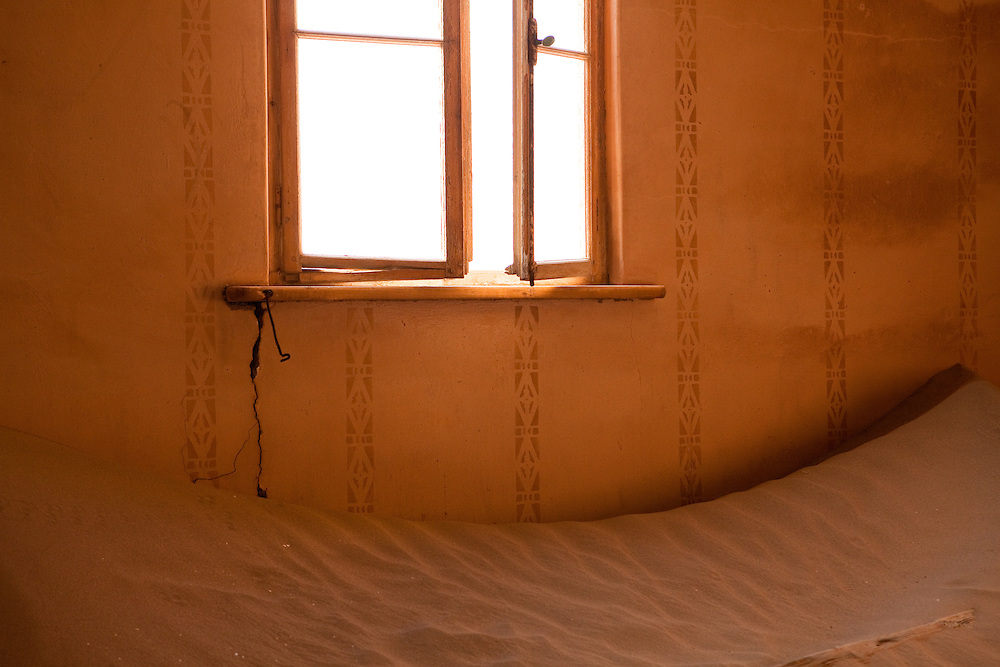 A window in a room of an abandoned sand-filled home in Kolmanskop, Namibia