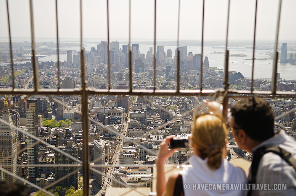 Tourists admiring the view from the top of the Empire State Building in New York City on a clear spring day.