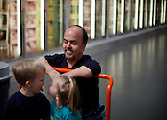 Chris Kotzian (top) watches his children make faces while shopping in Thornton, Colorado March 25, 2010.  Chris and son Adam, 6 (L) are both achondroplasia dwarfs while daughter Avery, 4 is average sized. Preferring to be called little persons Chris is active in the Little People of America, the only dwarfism support organization that includes all 200+ forms of dwarfism.  REUTERS/Rick Wilking (UNITED STATES)