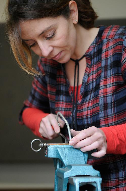 Frau beim Feilen eines Schlüssels   |  woman rasping a metal key