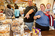 Apr. 3, 2009 -- MESA, AZ: KATRINA HALL, her husband, TIM HALL and their son, ZANE HALL, from Tempe, AZ, choose baked goods at the United Food Bank in Mesa, AZ. Hall said he drives a tourist bus but as the tourism and leisure industry has suffered in the recession his work in disappearing and in March he only work five days.  A spokesperson for the United Food Bank in Mesa, AZ, said demand has increased by more than 100 percent in the last year. She said that at this time in 2008, about 175 people a week (the food bank is open one day a week) bought 200 boxes a food but now they were seeing about 350 people per week and they were buying 400-450 boxes of food per week. Each box of food cost $16 and contains enough food for five meals for two people, including meat, fruit and vegetables and starches. In addition to the food boxes, the food bank gives away perishables, like fresh baked goods and produce, that are donated by Phoenix area grocery stores and food producers. She said the number of donations to the food bank have increased as the economy has worsened but each donation is smaller and the gap between donations and what the food bank needs is widening.    Photo by Jack Kurtz / ZUMA Press