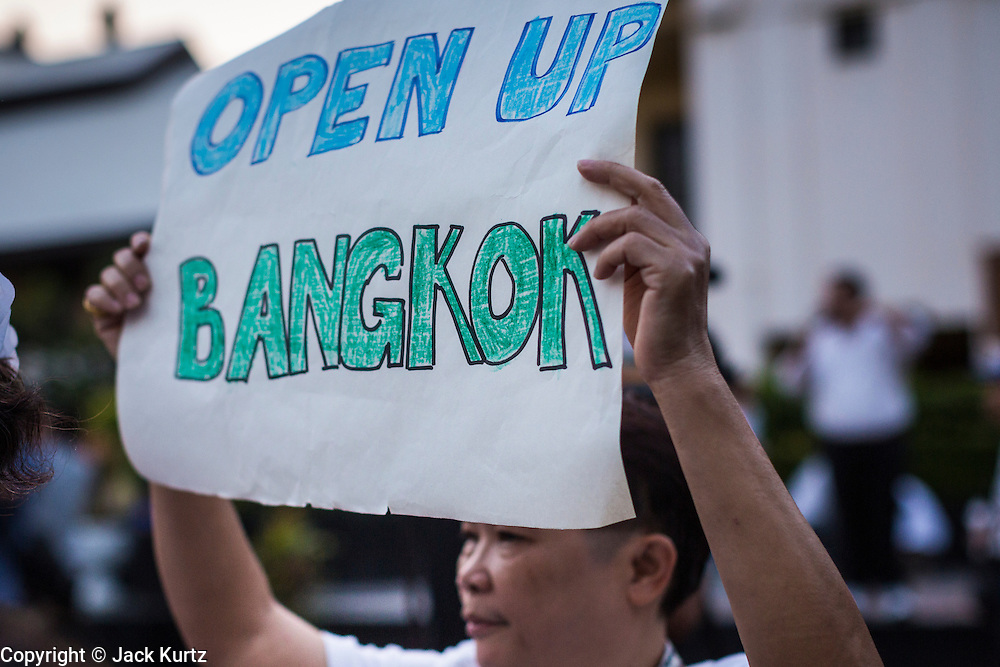 "12 JANUARY 2014 - BANGKOK, THAILAND:  A man carries a sign calling to keep Bangkok open. His sign is a response to anti-government protestors who want to shut Bangkok down. About 500 people from all walks of Thai life came to a candlelight vigil at Thammasat University. They prayed for a peaceful resolution to the political conflict in Thailand. They finished the vigil by singing the John Lennon song ""Imagine."" Anti-government protestors are expected ""Shutdown Bangkok"" Monday. There were reports Sunday evening that some intersections were already being blocked.      PHOTO BY JACK KURTZ"