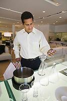 Man Examining Kitchenware in furniture store