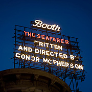 "A large neon sign atop the Booth Theater advertises ""The Seafarer,"" a hit broadway play."