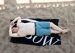 © Licensed to London News Pictures. 25/07/2019. Skegness, Lincolnshire, UK. Skegness seaside resort swelters under the summer heat. Staying in the shade of the pier in the midday sun. Photo credit: Dave Warren/LNP