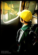Schoolboy in yellow cap gazes at his reflection in window on train's door on way home; Nikko. Japan
