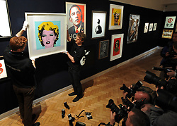 © Licensed to London News Pictures. 23/03/2012. London, UK. Photographer's take pictures of Bonham's staff George Foren (L) and Matthew Fancy hang one of the highlights of the sale, a screen print of British supermodel Kate Moss, 2005, inspired by Andy Warhols iconic Marilyn Monroe series, which has been estimated at £30,000  50,000. A photocall of Bonham's Urban Art Sale including Seventeen art works by the celebrated graffiti artist, Banksy, which are to be sold at Bonhams, London, ahead of the Urban Art Sale, which takes place on 29 March 2012. . Photo credit : Stephen SImpson/LNP