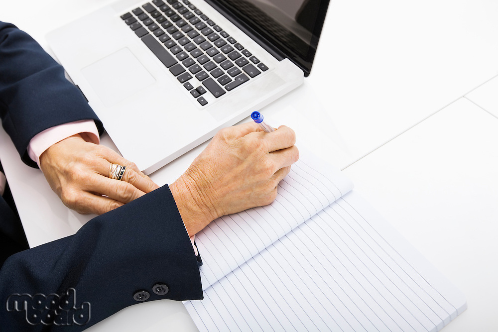Cropped image of businesswoman with laptop writing in notebook on office desk