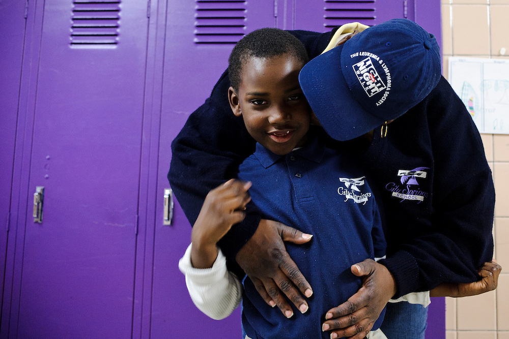 Photo copyright 2009, Matt Roth<br /> Wednesday, February 29, 2012<br /> <br /> City Springs School first grader Jahmal Harrison, gets a hug from his mother Tameka Harrison, in the school's hallway after his after school tutoring classes have ended Wednesday, February 29, 2012. Tameka, who can't work because of an injury, frequently volunteers at the school where poverty is the norm. Ninety-six percent of the student body qualifies for free lunches. Tameka and Jahmal used to live in one of the close by housing projects, but have been homeless for the last two months. They're currently staying at Sarah's Hope Shelter in West Baltimore.