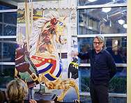 Garden City, New York, USA. March 9, 2019. Artist MICHAEL WHITE, gesturing toward his mural of the lead horse of historic Nunley's Carousel, gives info about the acrylic mural during its Unveiling Ceremony held at Nunley's Carousel Pavilion, Long Island. The mural, an approx. seven feet tall by five feet wide, 7'x5', will be installed on a trestle pillar outside Baldwin Train Station.