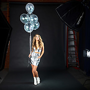 Behind the scenes photo of fashion model, Brenna Smith with silver party balloons. By Gerard Harrison. Image Theory Photoworks