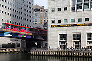 Commuters and city works walk past the FTSE 100 ticker on the side of the Thompson Reuters building in the financial district of Canary Wharf, London, England, United Kingdom. A Docklands light railway (DLR) train travels out from Canary Wharf station across a bridge over the Middle Dock of the River Thames.