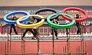 Workers removing the Olympic logo after the Olympic torch relay ceremony (Beijing, China).