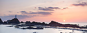 Sunset panorama of Corbière Lighthouse on the south west tip of Jersey. Channel Islands.