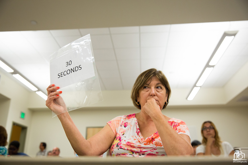 "Yolie Garcia holds up a ""30 Seconds"" sign to let contestants know they are running out of time in their response during the Milpitas Unified School District Board of Education forum at the Barbara Lee Senior Center in Milpitas, California, on October 2, 2014. (Stan Olszewski/SOSKIphoto)"