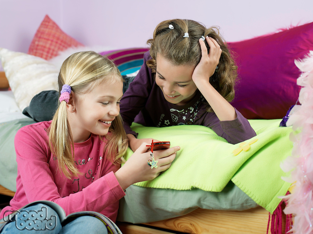 Smiling girls in bedroom looking at mobile phone