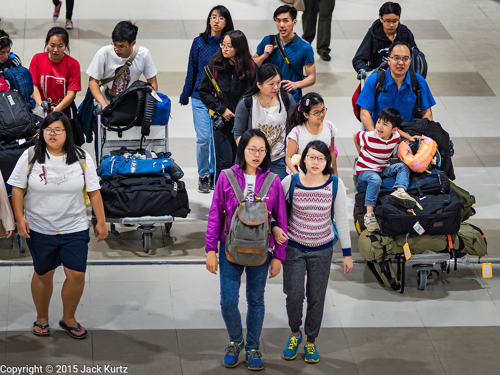 """24 DECEMBER 2015 - BANGKOK, THAILAND: Passengers  walk through the arrival hall in the new domestic terminal at Don Muang (also spelled Don Mueang) International Airport. The new terminal had its """"soft"""" opening Dec. 24. Don Muang is the airport used by low cost airlines serving Bangkok and is now the largest airport in the world for low cost carriers. In 2014, more than 21million passengers used Don Muang. Don Muang International Airport is the oldest airport in Asia and one of the oldest airports in the world. It started functioning as an airfield in 1914.     PHOTO BY JACK KURTZ"""