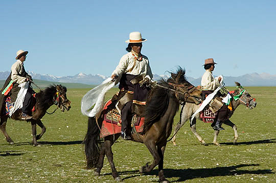 Northern Tibetans in traditional herdsmen dress with decorated horses. Tibet. Asia.