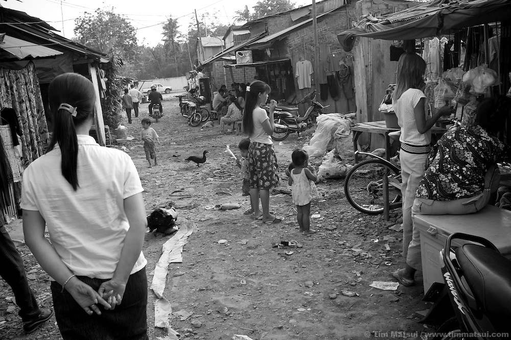 """Ouch Vanna, a Social Work Team Leader for the non governmental organization """"Acting for Women in Distressing Situations"""" (AFESIP), walks through a slum where the agency conducts outreach and provides services in Phnom Penh, Cambodia. The permanent structure, a decaying four story building known simply as 'The Building', was built in the 1960's as transitional housing and now hosts a shantytown where many of the city's poor live, including many prostitutes, and is believed to have the highest rate of HIV infection in the city. AFESIP hands out free condoms, instructs prostitutes on HIV prevention, and conducts outreach in case the prostitutes need medical services, choose to leave their profession, or can report on cases of sex trafficking. AFESIP offers housing, education, training, and counseling for women who are victims of sex trafficking, worked as prostitutes, or are escaping domestic violence. Founded by Somaly Mam, who herself was once a prostitute and victim of trafficking and domestic abuse, AFESIP has three facilities in Cambodia and works with other NGO's to provide long term care for the women."""