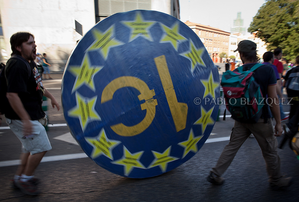 A protester runs with a large euro foam coin over people in Madrid on October 15, 2011 during a protest against the global economic crisis. Organizers claim 950 protests held in over 80 countries. Spain.