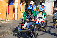 Tricycle rickshaws are a popular way for tourists to travel through the streets of the old town of Hoi An, Vietnam.