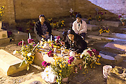 A family lights candles at the gravesite of a relative at Xoxocatian cemetery decorated with flowers and candles for the Day of the Dead Festival known in spanish as Día de Muertos on October 31, 2014 in Oaxaca, Mexico.
