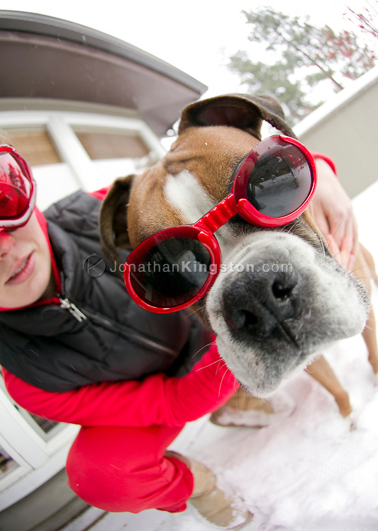 Close up of a young woman and a boxer dog wearing goggles in the snow. (releasecode: jk_mr1033) (Model Released)