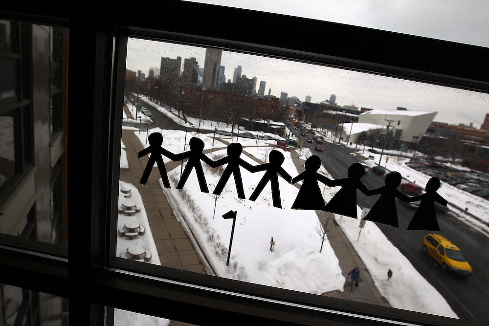 3/7/11 3:33:54 PM -- Minneapolis, MN, U.S.A.---.Paper doll cut-outs hang on the window of a StepUP apartment at Augsburg College facing the skyline of downtown Minneapolis March 7, 2011.  Applicants for the chemical-free living space are required to have at least six months of sobriety..---.Photo by Courtney Perry, Freelance.