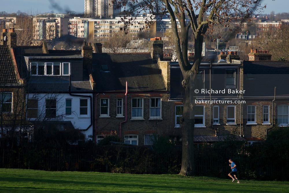 A male jogger runs uphill through his local park in the London Borough of Lambeth.