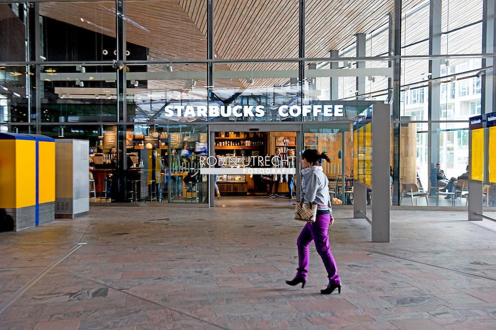 ROTTERDAM - Een starbucks koffie zaak op het centraal station van Rotterdam waar mensen koffie drinken en op hun computer en labtop werken . Starbucks vestiging op station Rotterdam Centraal COPYRIGHT ROBIN UTRECHT