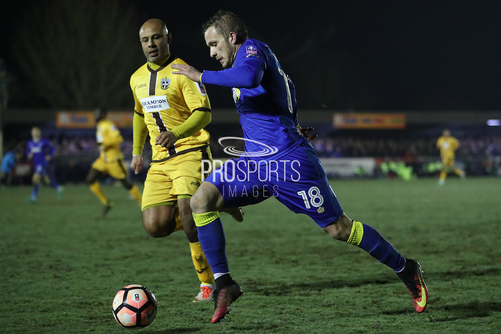 AFC Wimbledon midfielder Dean Parrett (18) and Sutton United Simon Downer (27) during the The FA Cup third round replay match between AFC Wimbledon and Sutton United at the Cherry Red Records Stadium, Kingston, England on 17 January 2017. Photo by Stuart Butcher.