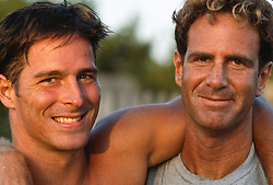 Two tan  men outdoors looking at camera