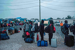 October 24, 2016 - Calais, France - Very early in the morning, the migrants from the white contaianer camp get ready to go to the wareghouse where they are registered to take the bus. Calais, France, on 24 October 2016. (Credit Image: © Guillaume Pinon/NurPhoto via ZUMA Press)