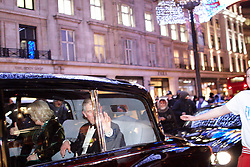 © under license to London News Pictures. 09/12/2010. Prince Charles waves and Camilla gives a thumbs up as a mob surrounds the Royal Convoy in Regent Street after it is accidentally driven into the middle of a riot. A rioter physically attacks his wife Camilla, Duchess of Cornwall, through an open window. The Rolls Royce carrying the couple is splattered with paint and a window is smashed. Photo credit should read Cliff Hide/LNP.