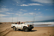 Angola, Namibe Province, Iona National Park. Flamingo lodge Fishing camp in the desert on the Atlantic coast. Driving 4x4 fishing vehicle on the beach in search of fish.<br /> <br /> Photo: &copy; Zute &amp; Demelza Lightfoot