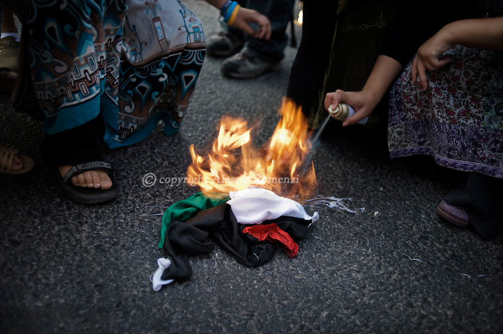 This picture shows Israeli settlers from the Israeli West bank settlement of Bet El next to Ramallah burning a Palestinian flag during the protest march against Palestinian bid for statehood at the United Nationson 20 September, 2011. ALESSIO ROMENZI