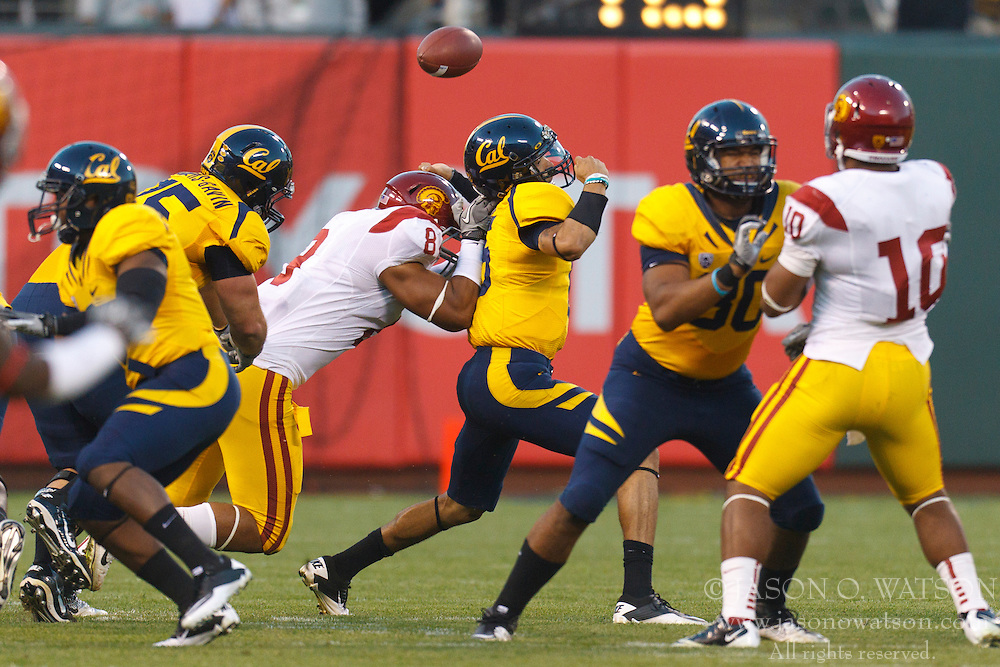 Oct 13, 2011; San Francisco CA, USA;  California Golden Bears quarterback Zach Maynard (15) fumbles the ball after a hit from Southern California Trojans defensive end Nick Perry (8) during the first quarter at AT&T Park.  Southern California defeated California 30-9. Mandatory Credit: Jason O. Watson-US PRESSWIRE