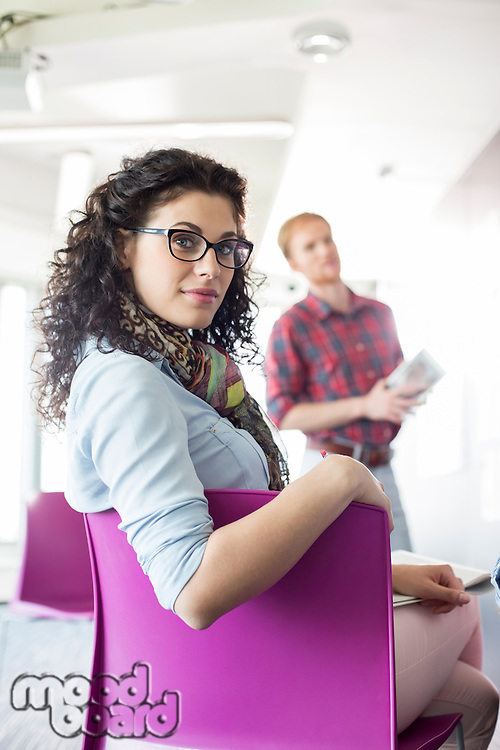 Portrait of confident businesswoman sitting on chair with colleague standing in background at creative office