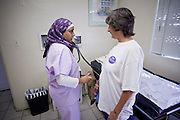 13 JUNE 2009 - PHOENIX, AZ: RN Saba Haroon takes the blood pressure of Tanya Gardino at the Cultural Cup walk in clinic. Gardino was there to see the doctor about shoulder pain. Gardino, who has no health insurance, was referred to the clinic by a Phoenix social service agency. The walk in clinic at the Cultural Cup Food Bank started two years ago when Cultural Cup founder Zarinah Awad wanted to expand the food bank's outreach and provide basic medical care for the people who use the food bank. The clinic sees, on average, 7 - 11 patients a week. Awad said that as the economy has worsened since the clinic opened and demand has steadily increased. She attributes the growth to people losing their jobs and health insurance. The clinic is staffed by volunteers both in the office and medical staff. Adults are seen every Saturday. Children are seen one Saturday a month, when a pediatrician comes in. Awad, a Moslem, said the food bank and clinic are rooted in the Moslem tradition of Zakat or Alms Giving, the giving of a small percentage of one's income to charity which is one of the Five Pillars of Islam.   PHOTO BY JACK KURTZ