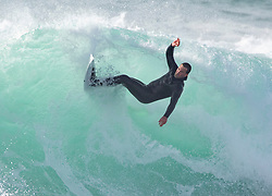 © Licensed to London News Pictures. 21/04/2020. Padstow, UK. A surfer catches a wave near Padstow on the north coast of Cornwall this afternoon during a period of warm weather set to continue for the rest of the week. Photo credit : Tom Nicholson/LNP