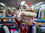 27 JANUARY 2017 - BANGKOK, THAILAND:  Chinese Lion dancers perform in a fabric shop owned by a Thai-Chinese family in Bangkok on Chinese New Year. 2017 is the Year of the Rooster in the Chinese zodiac. This year's Lunar New Year festivities in Bangkok were toned down because many people are still mourning the death Bhumibol Adulyadej, the Late King of Thailand, who died on Oct 13, 2016. Chinese New Year is widely celebrated in Thailand, because ethnic Chinese are about 15% of the Thai population.      PHOTO BY JACK KURTZ
