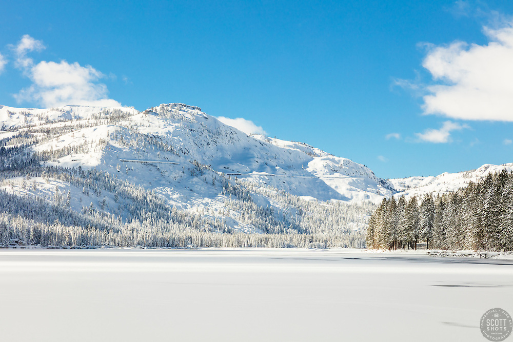 """""""Snow Covered Donner Lake 1"""" - Photograph of a mostly iced over and snow covered Donner Lake, Donner Summit can be seen in the background."""
