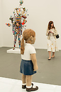 "A wooden statue of a girl by Claudette Schreudes seems to look at a fair attendee. In the background is a colorful piece by Nick Cave, titled ""Soundsuit."""